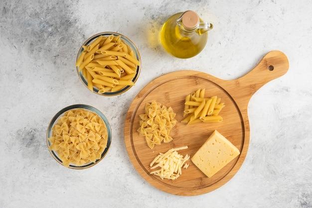 Surowy makaron, olej i ser na marmurze.