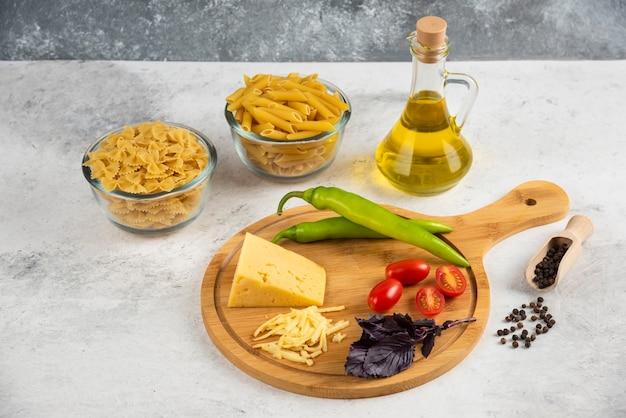 Surowy makaron, olej, ser i świeże warzywa na marmurze.
