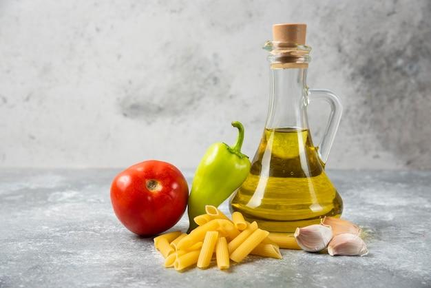 Surowy makaron penne z butelką oliwy z oliwek i warzywami na marmurowym stole. ścieśniać.
