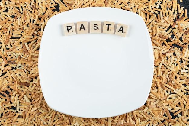 Surowy makaron porozrzucany po białym talerzu z drewnianymi literami.