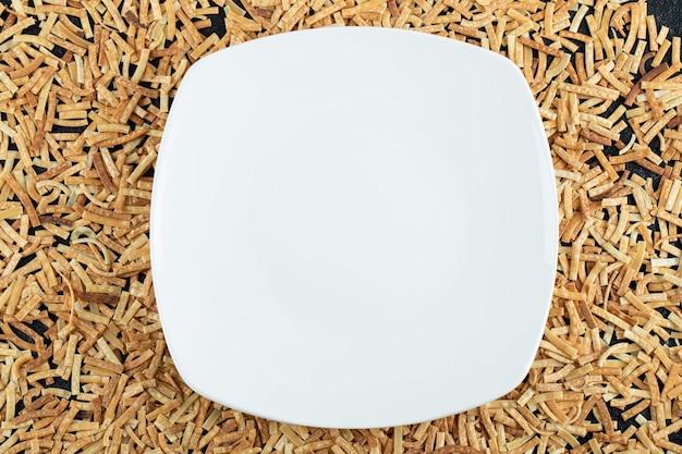 Surowy makaron rozrzucony po białym talerzu.