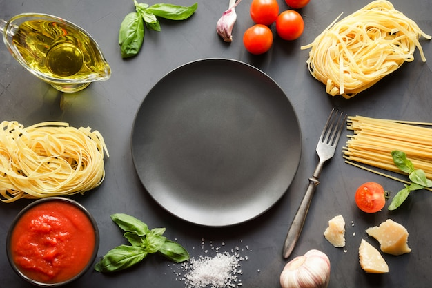 Surowy makaron, spaghetti, pomidory, bazylia, parmezan do gotowania dań kuchni śródziemnomorskiej.