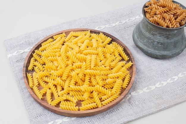 Surowy makaron spirali w filiżance i talerzu na obrusie