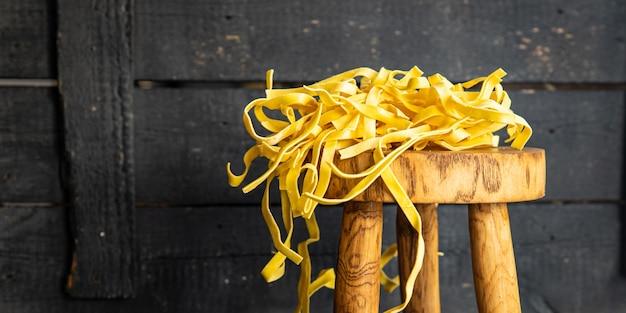 Surowy makaron tagliatelle do gotowania w domu ręcznie robiony z pszenicy durum świeży posiłek przekąska na stole kopia przestrzeń