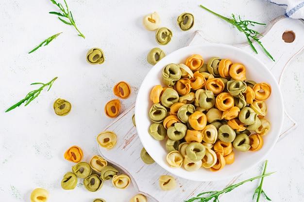 Surowy makaron tortellini wypełniony serem w białej misce. włoski makaron. widok z góry, płasko ułożony, nad głową