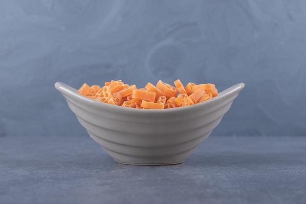 Surowy makaron w kształcie serca w ceramicznej misce.