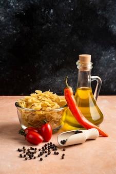 Surowy makaron, warzywa i butelka oleju na pomarańczowym stole.
