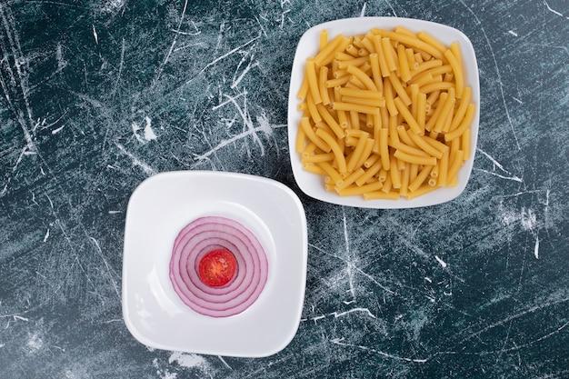 Surowy makaron z kawałkami cebuli i małych pomidorów na tle marmuru. wysokiej jakości zdjęcie