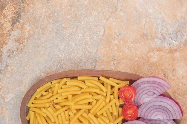 Surowy makaron z plastrami cebuli i małym pomidorem na marmurowej przestrzeni.