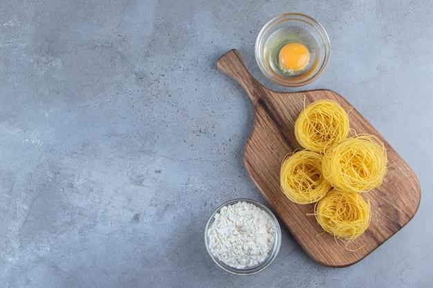 Surowy makaron z suchym gniazdem z surowym jajkiem i szklaną miską mąki na kamiennym tle.