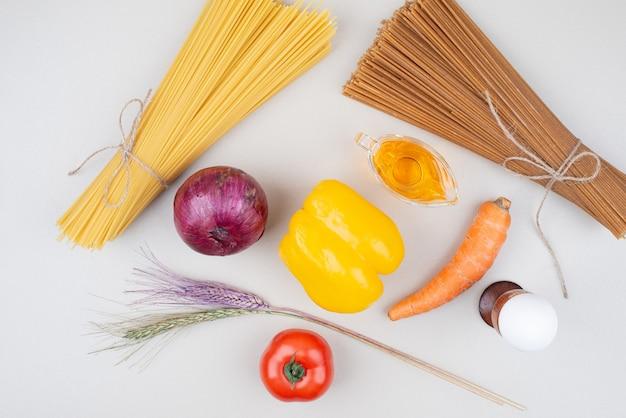 Surowy makaron z warzywami na białej powierzchni