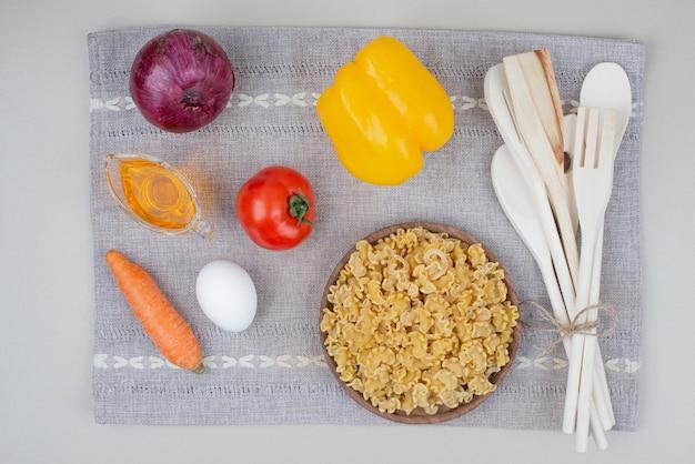 Surowy makaron z warzywami na drewnianym talerzu na obrusie