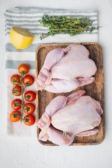 Surowy mały młody cały kurczak z ziołami i składnikami, na białym tle, widok z góry