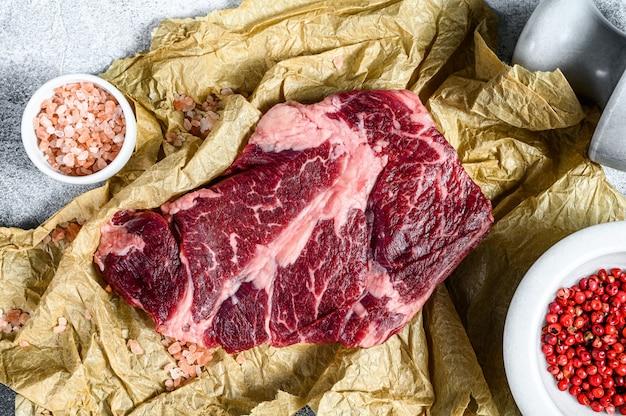 Surowy marmurkowaty stek wołowy na desce do krojenia. ekologiczne mięso hodowlane czarne angus.