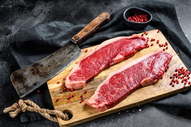 Surowy marmurkowaty stek wołowy na desce do krojenia. widok z góry