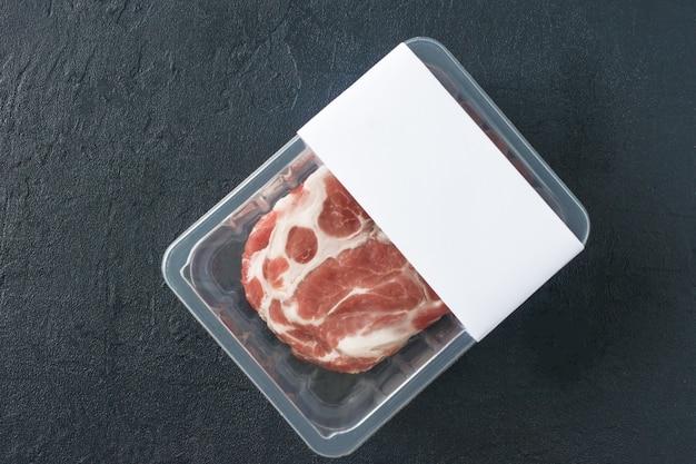 Surowy marmurkowy stek wieprzowy w opakowaniu próżniowym na czarnym tle, widok z góry, makieta logo dla projektu.