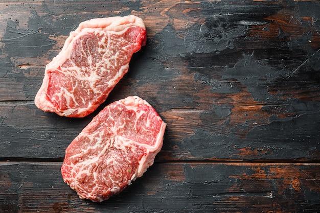 Surowy marmurkowy stek wołowy, cięte z ekologicznego mięsa z górnej części. na ciemnym tle drewnianych, widok z góry z miejscem na tekst.