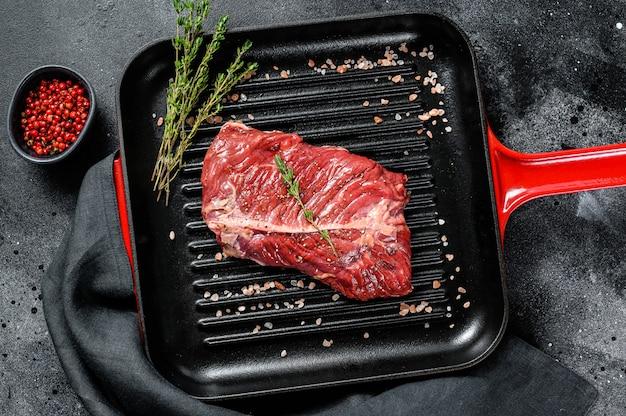 Surowy marmurkowy stek wołowy na patelni grillowej. czarne tło. widok z góry