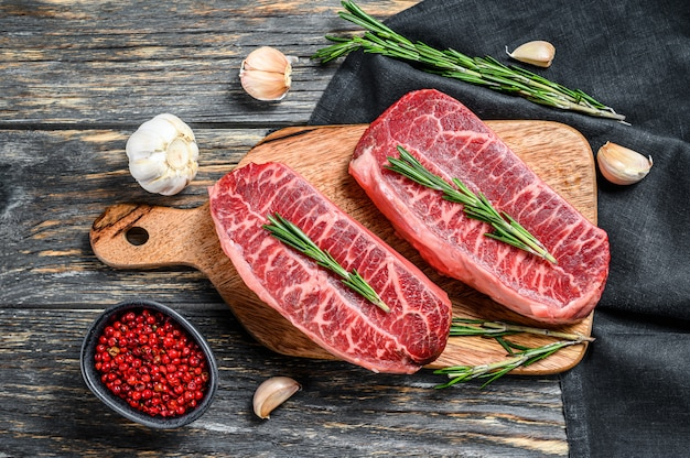 Surowy marmurkowy stek wołowy, stek z mięsem na ostrzu na czarno. widok z góry
