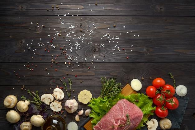 Surowy mięso z składnikami na drewnianym tle
