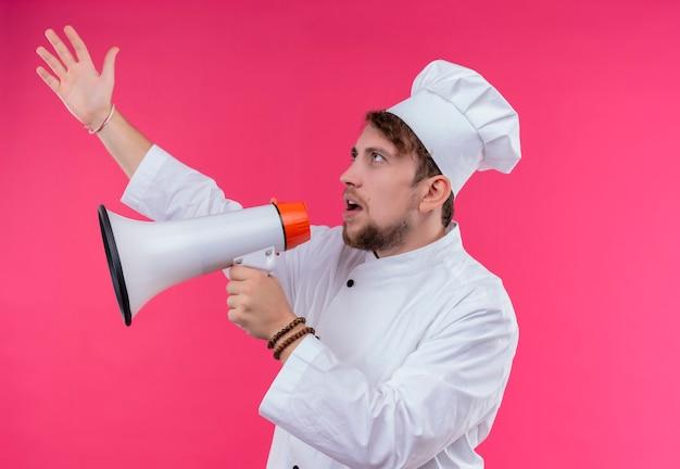 Surowy, młody, brodaty szef kuchni w białym mundurze mówiący przez megafon z podniesioną ręką na różowej ścianie