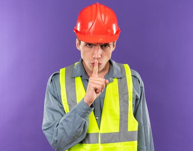 Surowy Młody Budowniczy Mężczyzna W Mundurze Pokazujący Gest Ciszy Odizolowany Na Niebieskiej ścianie Premium Zdjęcia