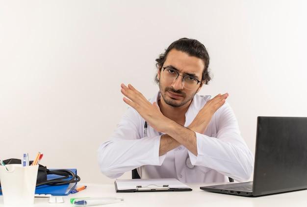 Surowy młody lekarz mężczyzna z okularami medycznymi na sobie szlafrok medyczny ze stetoskopem