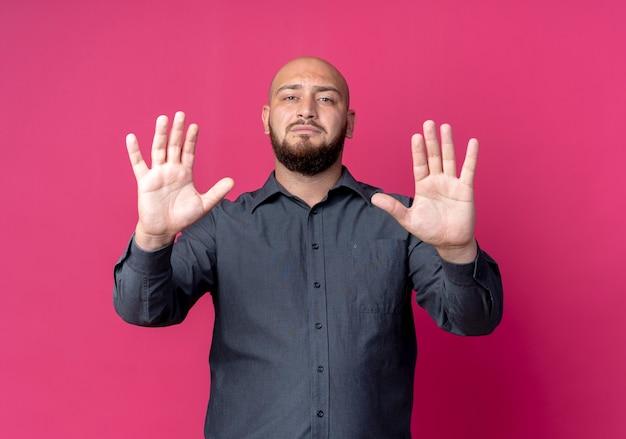Surowy, młody, łysy mężczyzna z call center wyciągając ręce z przodu, gestykulując stop odizolowany na szkarłatnej ścianie