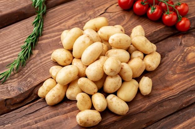 Surowy młody mały ziemniak z rozmarynem i pomidorkami koktajlowymi na drewnianym tle