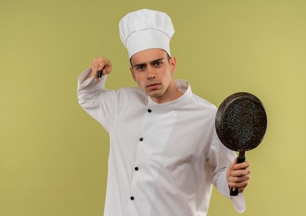 Surowy młody mężczyzna kucharz ubrany w mundur szefa kuchni trzymając patelnię podnosząc nóż w ręku