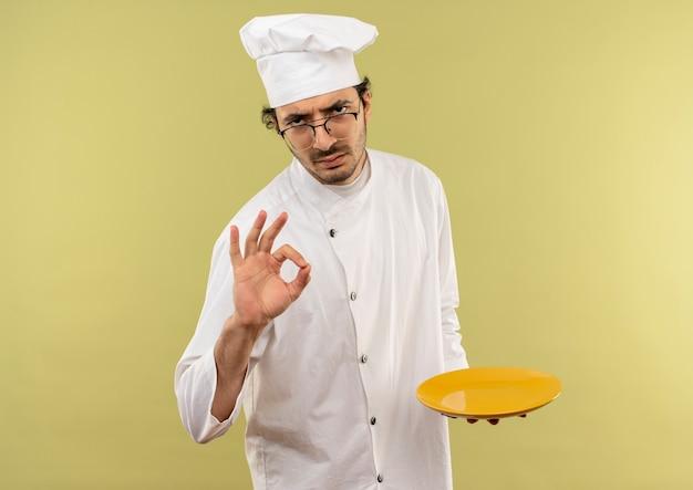 Surowy młody mężczyzna kucharz w mundurze szefa kuchni i okularach, trzymając talerz i pokazując gest okey na zielonej ścianie