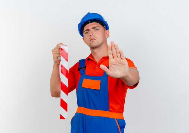 Surowy młody mężczyzna w mundurze i hełmie ochronnym, trzymając taśmę klejącą i pokazujący gest stopu na białym tle