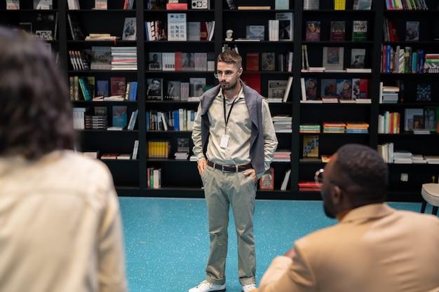 Surowy młody nauczyciel lub trener stojący przed międzykulturowymi uczniami