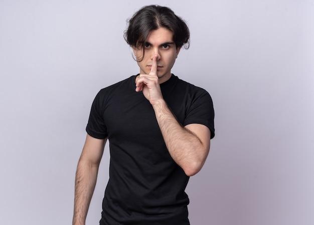 Surowy młody przystojny facet ubrany w czarną koszulkę pokazując gest ciszy na białym tle na białej ścianie