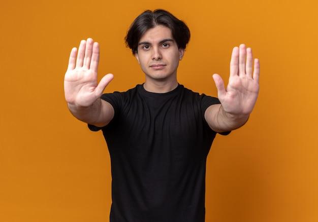 Surowy młody przystojny facet ubrany w czarną koszulkę pokazujący gest stopu na białym tle na pomarańczowej ścianie