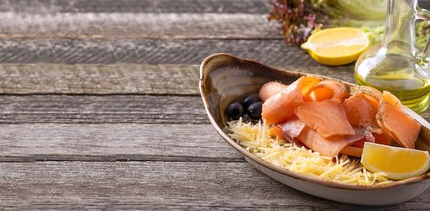 Surowy mrożony łosoś z serem, cytryną i oliwkami
