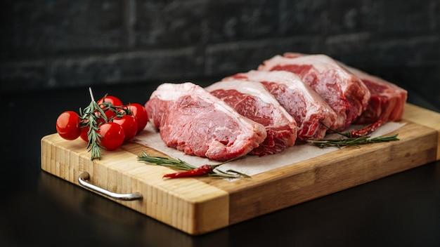 Surowy niegotowany stek z rostbefu w nowym jorku na drewnianej desce z pomidorami i rozmarynem