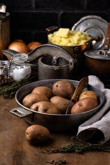 Surowy niegotowany ziemniak w starym garnku vintage