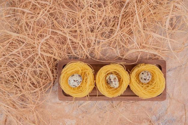 Surowy okrągły makaron z jajkami przepiórczymi na tle marmuru. wysokiej jakości zdjęcie
