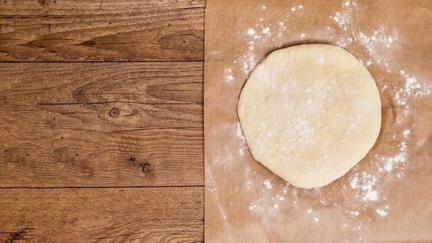Surowy okrągły spłaszcz ciasto na pergaminie papieru na drewnianym stole