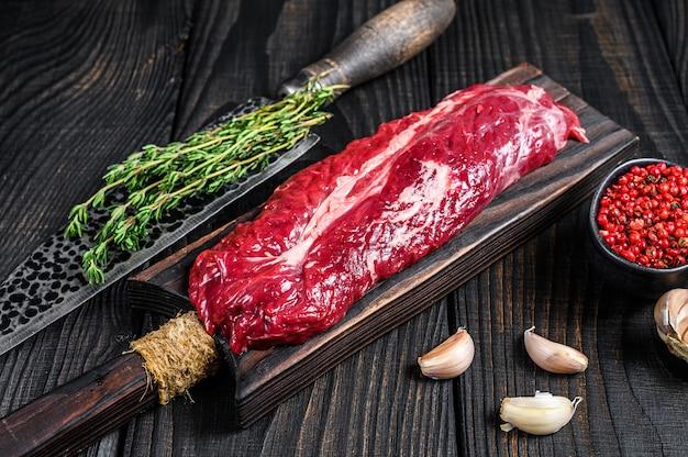 Surowy onglet wiszący stek wołowy przetargu na drewnianą deskę do krojenia. czarne drewniane tło. widok z góry.
