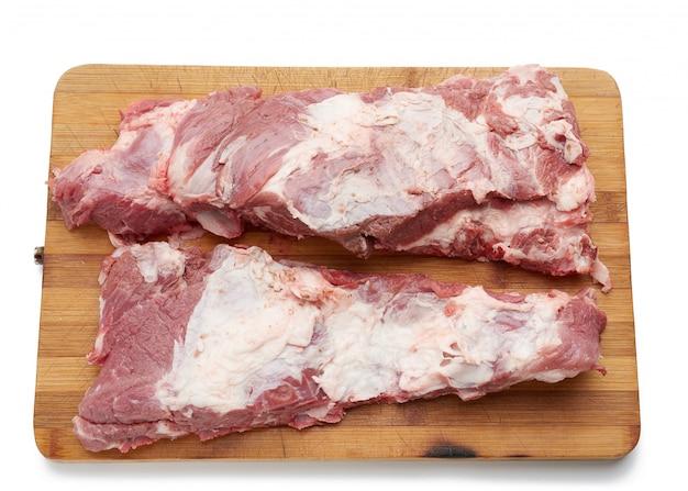 Surowy pasek wieprzowiny na żebrach z warstwami tłuszczu na drewnianej desce do krojenia