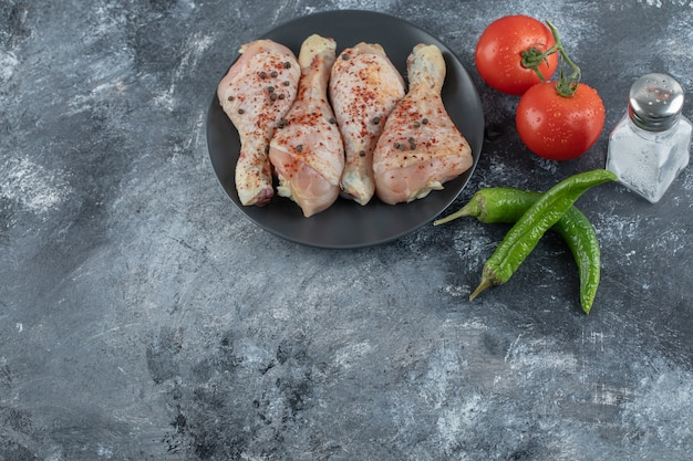 Surowy pikantny podudzie z kurczaka z pomidorami i papryką na szarym tle.
