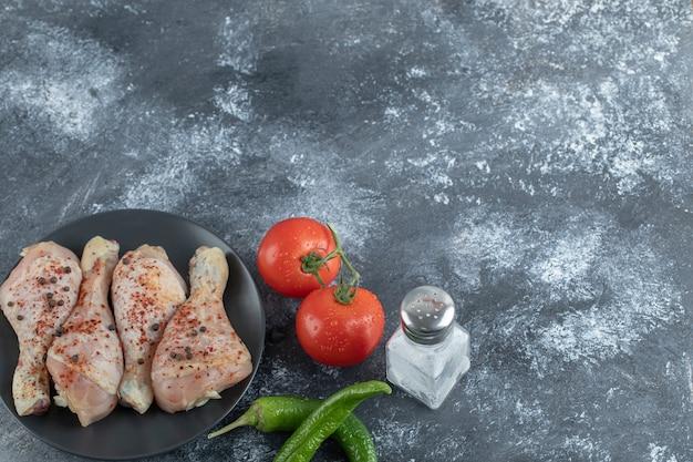 Surowy pikantny podudzie z kurczaka z pomidorami, pieprzem i solą na szarym tle.