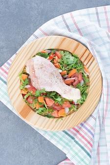 Surowy podudzie z kurczaka i pokrojone warzywa na drewnianym talerzu.