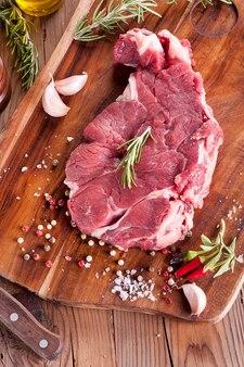 -surowy pokrojony rozmaryn mięsny na tle drewna