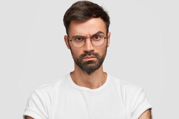 Surowy, poważny, niezadowolony szef mężczyzna unosi brwi z gniewnym, niezadowolonym wyrazem twarzy, czegoś nie lubi, wyraża negatywne emocje, ubrany niedbale, pozuje przy białej ścianie.