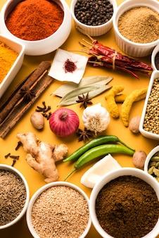 Surowy proszek indyjskich przypraw w białych miseczkach na kolorowym tle, selektywne skupienie