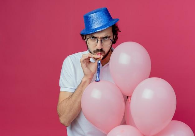 Surowy przystojny mężczyzna w okularach i niebieskim kapeluszu, trzymając balony i dmuchający gwizdek na białym tle na różowym tle