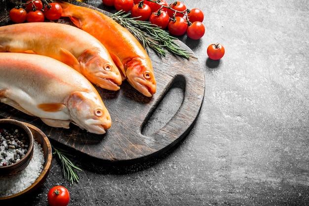 Surowy pstrąg rybny na desce do krojenia z rozmarynem, przyprawami i pomidorami. na ciemny rustykalny